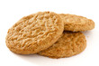 Detail of three crispy golden oat biscuits on white