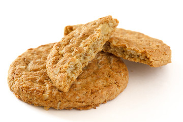 Two crispy golden oat biscuits on white, one broken in half