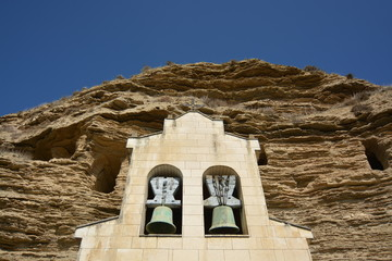Cuevas en la montaña con campanario en primer plano