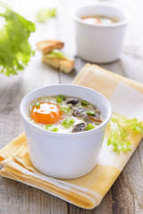 Baked eggs with mushrooms on wooden table