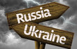 Russia and Ukraine wooden sign on a bad weather
