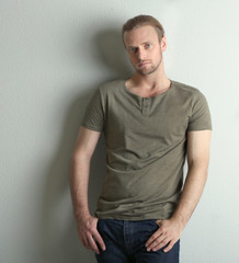 Fashion young model poses over wall with shadow