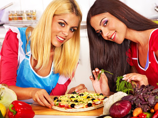 Women cooking pizza.