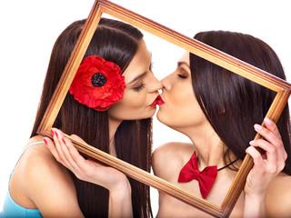 Two sexy lesbian women kissing in art frame.