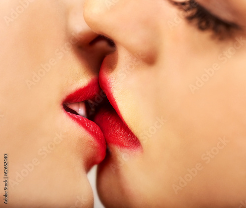 Face lesbian women kissing in erotic foreplay game
