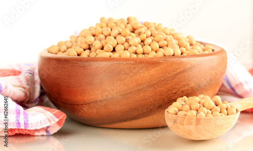 Raw soybeans in bowl on color napkin, isolated on white