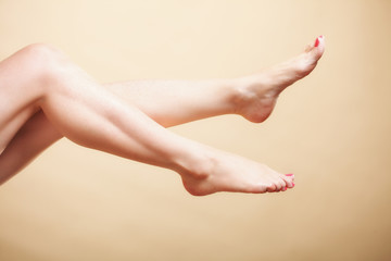Beautiful long naked woman girl legs on orange