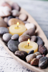 Spa stones and candle in decorative bowl,