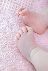 baby girl feet on pink blanket