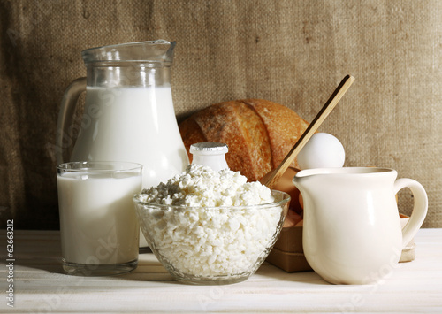Tasty dairy products on wooden table, on sacking background