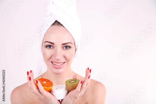 Beautiful young woman holding exotic fruits and bowl with