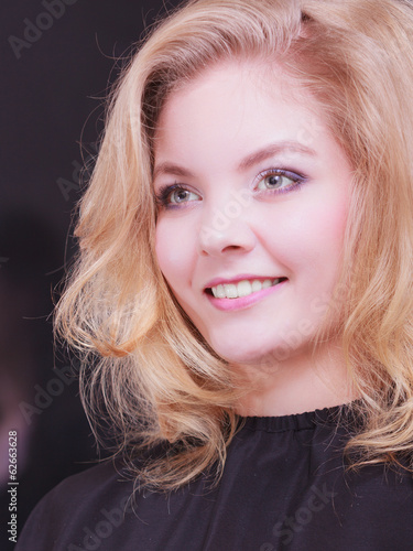 Beautiful girl with blond wavy hair in hairdressing beauty salon