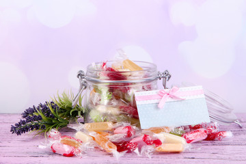 Tasty candies in jar with card on table on bright background