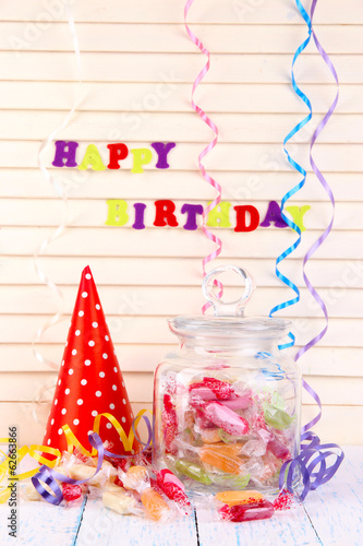 Tasty candies in jar with party hat