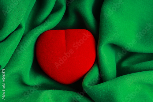 Red jewel box heart gift present on green fabric wavy cloth