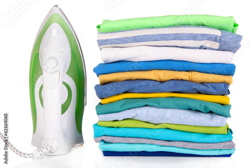 Iron and pile of colorful clothes isolated on white