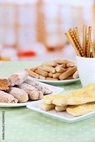 Variety of bread sticks on table, on bright background