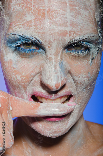 Woman with paint on his face biting her finger