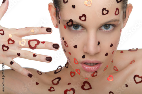 Young woman with hearts on face and hand