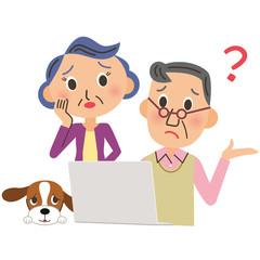 パソコンを見て困っている老夫婦