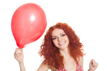 Joyful redhead girl holding red balloon