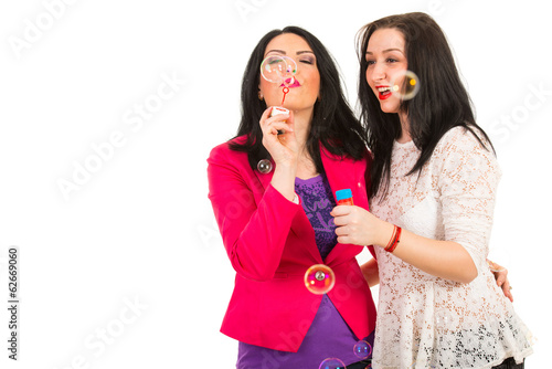 Happy friends women blow out bubbles