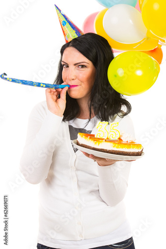 Birthday woman blowing into party horn blower