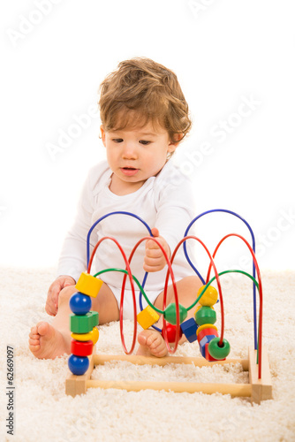 Little boy playing with wooden toy