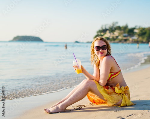 young woman with fruit cocktail sitting on beach