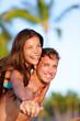Couple fun on beach - man giving piggyback