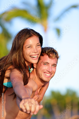 Couple fun on beach - man giving piggyback