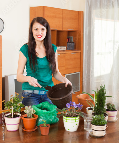 Happy woman transplanting potted flowers