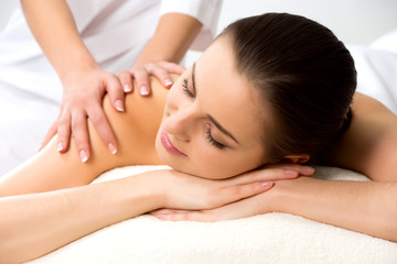 Masseur doing massage on the back of woman in the spa salon.