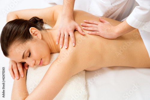 Leinwanddruck Bild Masseur doing massage on the back of woman in the spa salon.