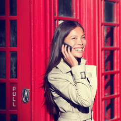 London woman on smart phone by red phone booth