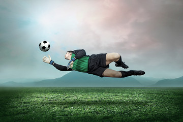 Goalkeeper with ball in action outdoors.