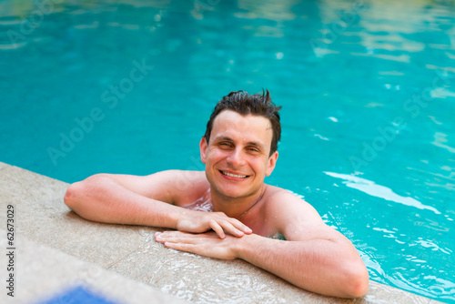 Young wet man posing in the swimming pool