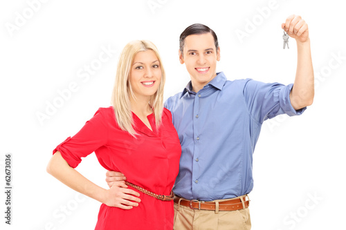 Happy young couple holding keys