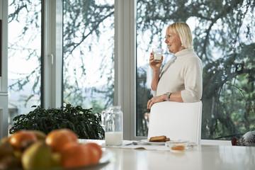 Portrait of senior woman having breakfast with milk