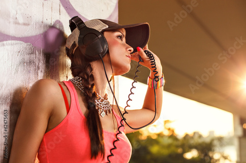 Beautiful young woman enjoying the music with headphones and wea