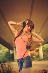 Beautiful hip hop woman with a cap and headphones listening to m