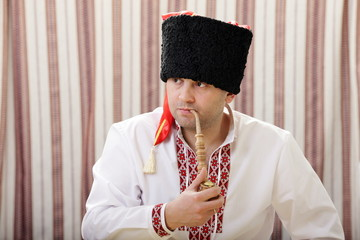 Ukrainian Cossack in national dress smokes a pipe
