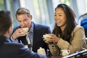 A Businesswoman And Two Businessmen Sitting In A Coffee Shop Having A Cup Of Coffee.
