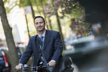 A Man In A Business Suit, Outdoors In A Park. Sitting On A Bicycle.
