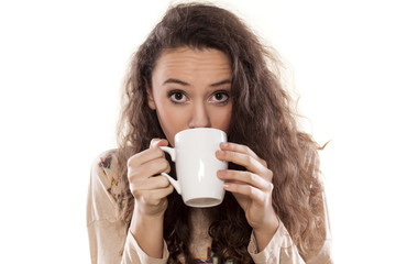 young girl drinking from a mug on white background