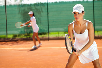 women playing doubles at tennis