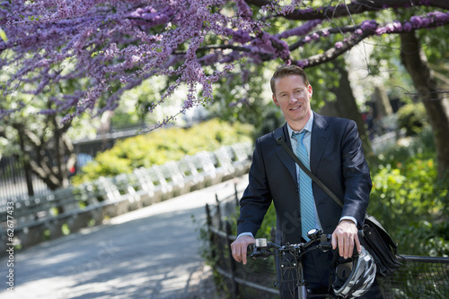 A Man In A Business Suit, On A Bicycle, With A Cycle Helmet In His Hands.