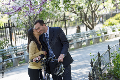 A Man In A Business Suit Astride A Bicycle. A Woman Kissing Him Goodbye.
