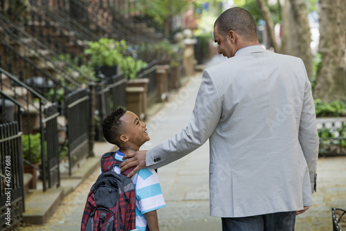 An Adult And A Child, A Father And Son, Walking Together On The Street In The City.