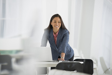 Business. A Woman Leaning Over A Desk Using A Laptop Computer.